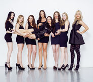 Many diverse women in line, wearing fancy little black dresses, party makeup, vice squad concept. Close up Stock Images