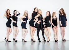 Many diverse women in line, wearing fancy little black dresses, royalty free stock images