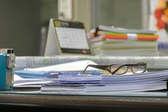Many documents are placed on the desk.Pen and goggles are placed stock image