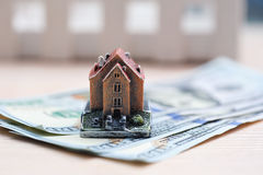 Many dollar banknotes and a house model; concept of buying a house stock photo
