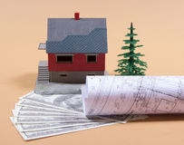 Many dollar banknotes and a house model. Concept of buying a house. Stock Images
