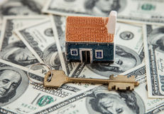 Many dollar banknotes, key and a house model Stock Photos
