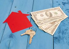 Many dollar banknotes, key and a house model. Concept of buying a house. Royalty Free Stock Photo