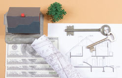 Many dollar banknotes, key and a house model. Concept of buying a house. Stock Photography