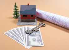 Many dollar banknotes, key and a house model. Concept of buying a house. Royalty Free Stock Image