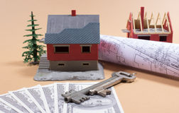Many dollar banknotes, key and a house model. Concept of buying a house. Stock Image
