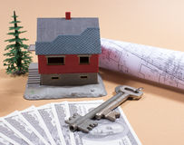 Many dollar banknotes, key and a house model. Concept of buying a house. Royalty Free Stock Photos