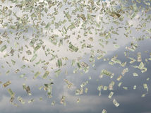 Many dollar bills falling. Dollar bills falling on a sky background Royalty Free Stock Image