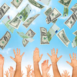 Many dollars falling on business people hands. On blue background stock images