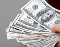 Many dollars falling on man's hand with money, isolated. Many dollars falling on man's hand with money Royalty Free Stock Photography