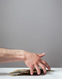 Many dollars falling on man's hand with money. Lying on the desk Royalty Free Stock Photo