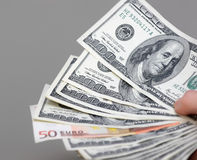 Many dollars falling on man's hand with money. Lying on the desk Stock Photo