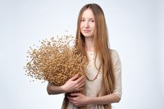 Many dried flowers of flax in the hands of a beautiful girl with lon hair. Dried flowers of flax in the hands of a beautiful girl with lon hair stock photo