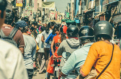 Many drivers on motorcycles moving past busy indian street of crowded indian city Royalty Free Stock Images