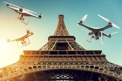 Many drones with digital camera flying around Tour Eiffel. 3D rendering Stock Photography
