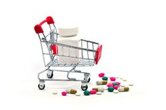 Many drugs and pills with white plastic bottle in shopping cart royalty free stock photo