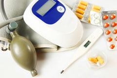 Many drugs with thermometer and blood pressure measurement device. Influenza. Many drugs with thermometer and blood pressure measurement device on light stock photos