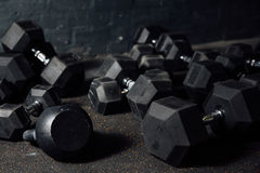 Many dumbbells lie randomly on the floor. Loft gym. Place for the text. Black wall Royalty Free Stock Photos