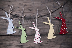 Many Easter Bunnies Hanging On Line. Five Colorful Easter Bunnies Hanging On A Line Which Are Dotted And Striped On Brown Wooden Vintage Or Rustic Background For stock image