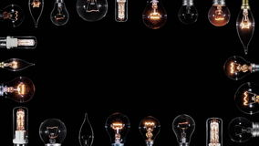 Many Edison lamps blinking over black, copyspace frame, looped stock video footage