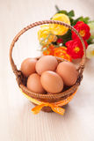 Many eggs in little basket with flowers on wooden table Stock Photography
