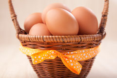 Many eggs in  little basket with yellow bow on wooden table Stock Images