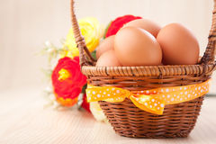 Many eggs in  little basket with yellow bow on wooden table with Stock Images