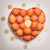 Many eggs smile and money. Chicken egg in heart box pink and the flower Stock Images