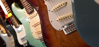 Many electric guitars hanging on wall in the shop Stock Photos