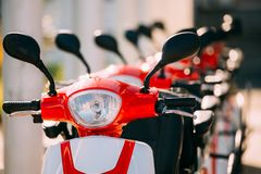 Many Electric Motorbikes, Motorcycles Scooters Parked In Row In City. Close Up Of Handlebars Of Many Electric Motorbikes, Motorcycles Scooters Parked In Row In Royalty Free Stock Image