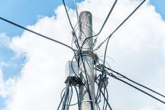Many electric wires on concrete street pole with internet or cell phone communication box and blue sky background stock images