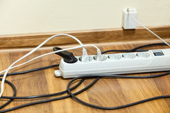 Many electrical cords connected to extension block Stock Image