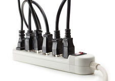 Many electrical cords connected to a power strip Stock Photos