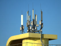 Many electronics aerials on yellow building top Stock Photography