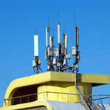 Many electronics aerials on yellow building top Stock Photos