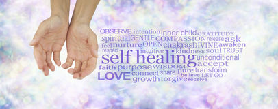 The many elements of Self Healing. Female hands in cupped position on a subtle pastel multicolored bokeh background with a purple SELF HEALING word cloud to the stock photo