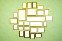 Many empty golden wooden frames with copy space on green wall. Royalty Free Stock Photography
