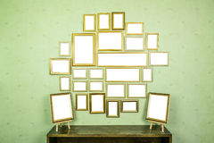 Many empty golden wooden frames with copy space on green wallpaper. Royalty Free Stock Photos
