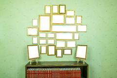 Many empty golden wooden frames with copy space on green wallpapered wall. Bookshelf with books. Royalty Free Stock Images