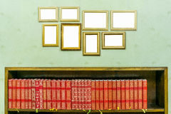 Many empty golden wooden frames with copy space on green wallpapered wall. Bookshelf, books. Royalty Free Stock Photo