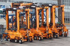 Many empty loaders stand on asphalt in seaport stock photos