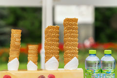Many empty wafer sweet cornets for ice cream on naturale green blurry background. Selective focus. Copy space. Real Royalty Free Stock Photography