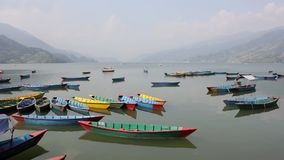 Many empty wooden colored boats on a smooth lake during the day against the backdrop of a mountain valley