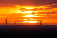 Sunset at wind turbines windmills offshore clean power farm near Stock Photos