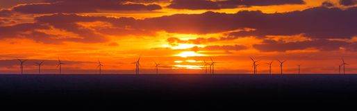 Panorama sunset sun at windmills offshore clean wind power farm Royalty Free Stock Photos