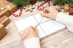 Many envelopes tied with rope. Close-up top view of famale hands with envelope. Pine cones and christmas decoration on old wooden. Table, desk stock photos