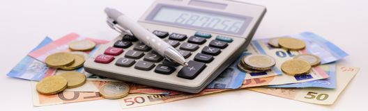 Many Euro banknotes and calculator. Laying on table Royalty Free Stock Image