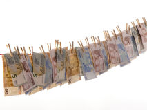 Many euro banknotes on a clothesline. On a white background Stock Photos
