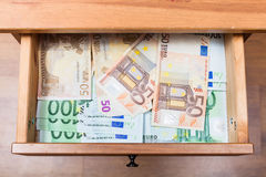 Many euro banknotes in open drawer. Top view of many euro banknotes in open drawer of nightstand Royalty Free Stock Photos