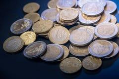 Many euro coins. On black background stock photos